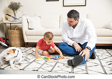 Father Watching Boy Playing With Toys By Dog At Home