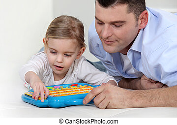 Father watching daughter play with electronic toy