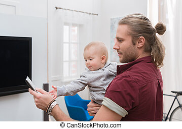 father watching TV with little baby boy at home
