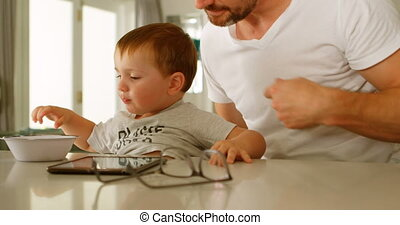 Father wearing clothe to son on table 4k - Father wearing...