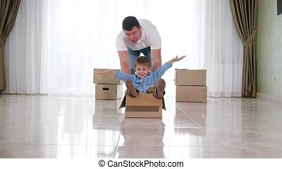 father wearing white shirt rides smiling son in craft box