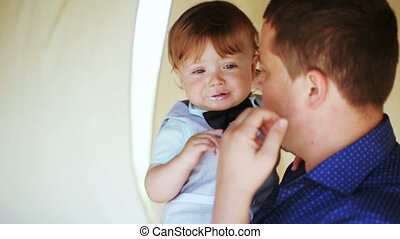 Father wipes his face with child