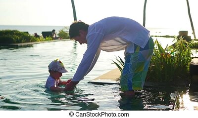 Father with a child playing in the pool next to the beach, sunset time. Tropical island
