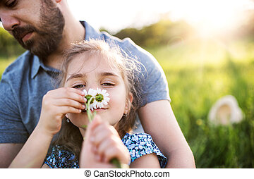 Father with a small daughter having fun in spring nature.