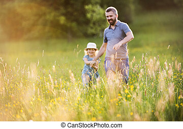 Father with a small daughter on a walk in spring nature.