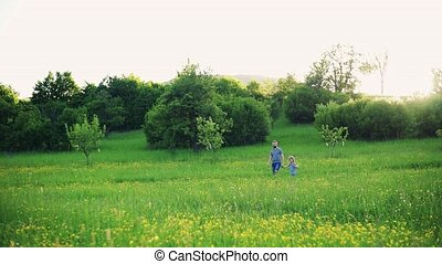 Father with a small daughter on a walk in spring nature. -...
