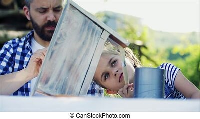 Father with a small daughter outside, painting wooden...