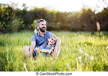 Father with a small daughter sitting on the grass in spring nature.