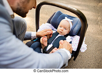 Father with baby daughter sitting in car safety seat.