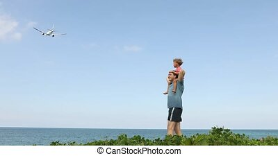 Father with boy on shoulders looking at flying plane