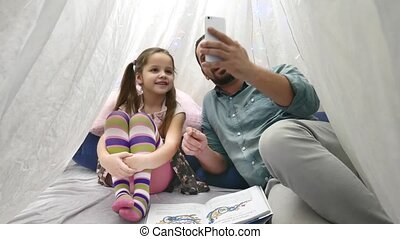 Father with cheerful little daugher playing with smartphone...
