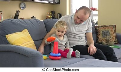 father with child daughter play with colorful education circles pyramid on sofa