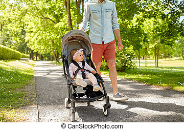 father with child in stroller at summer park
