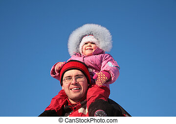 father with child on shoulders in winter