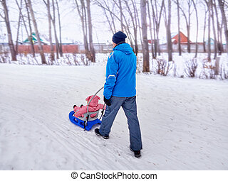 Father with child walk in the winter the sledge on snow.