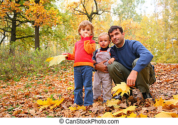 Father with children in autumn wood