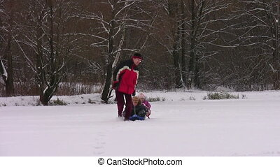father with children on sleds