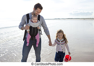 Father with Children on the Beach - Young father walking on...