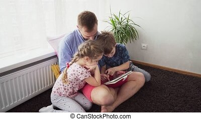 father with children using a tablet