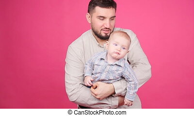 Father with cute little son over pink background - Father...