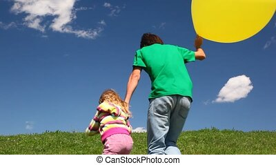Father with daughter and bubble holding hands down hill