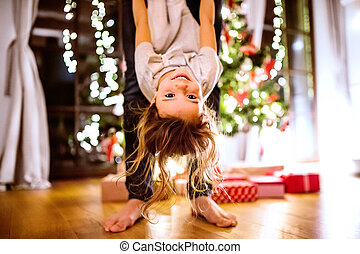 Father with daughter at Christmas tree holding her upside ...