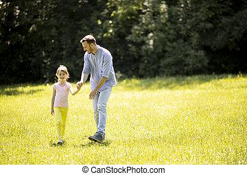 Father with daughter having fun on the grass at the park