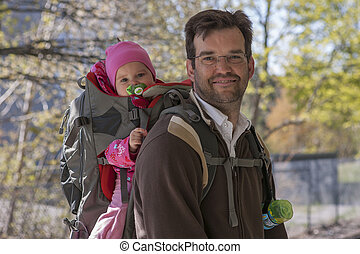 Father with daughter in backpack carrier