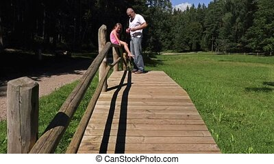 Father with daughter on wooden bridge in the park