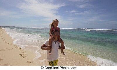 Father with daughter with child on the beach.
