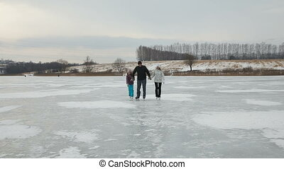 Father with daughters ice skating on frozen lake