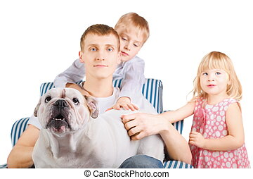 father with english bulldog is sitting on a chair. his son and daughter near him. focus on dog's nose.