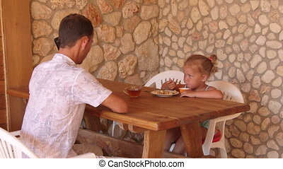 Father with her daughter have breakfast in outdoor summer kitchen