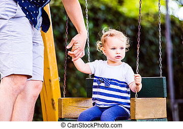 Father with his daughter on swing in a park.