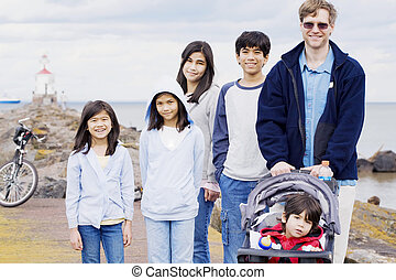 Father with his five children at the beach, interracial family