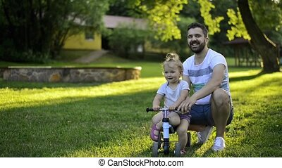 Father with his little daughter on bicycle pushing her