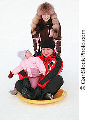 father with his little daughter on snow saucer at snow, mother standing near them, winter, focus on girl