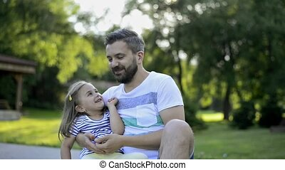 Father with his little daughter outside in park