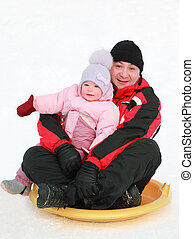 father with his little daughter rolling on snow saucer at snow at winter, focus on girl