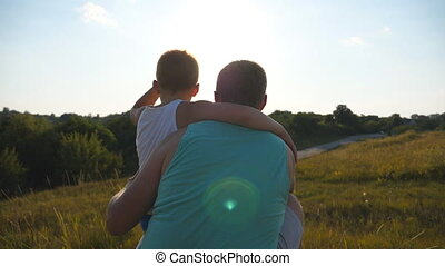 Father with his little son spending time together outdoor at sunset. Dad and child sitting at green grass on the hill and looking to the nature around them. Slow motion Rear back view