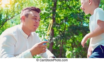 Father with his son blowing soap bubbles, fun family pastime, a child having fun with his dad