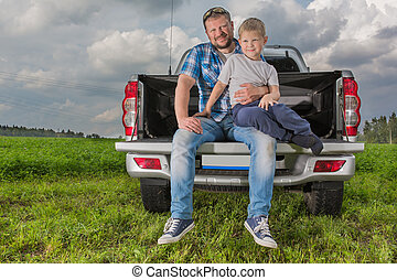 Father with his son sitting on car trunk
