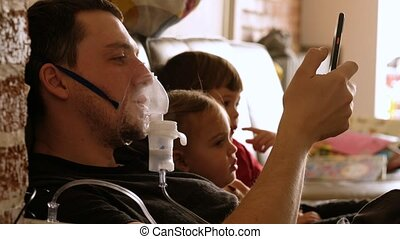 Young man in casual wear and inhaler mask resting on sofa and using mobile phone while little kids sitting nearby and watching tv