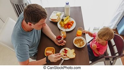 Father with kid having breakfast together
