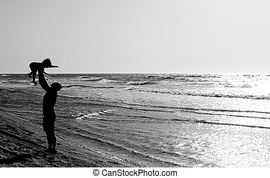father with kid on the beach at sunset