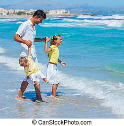Father with kids on beach