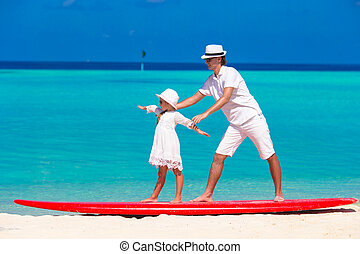 Father with little daughter at beach practicing surfing position