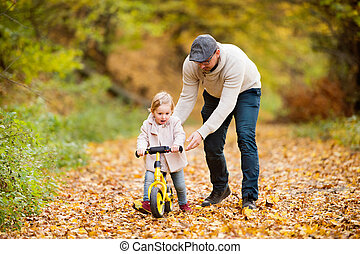 Father with little daughter cycling in autumn park. - Young...