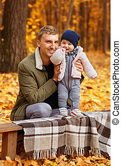 father with little daughter in autumn park