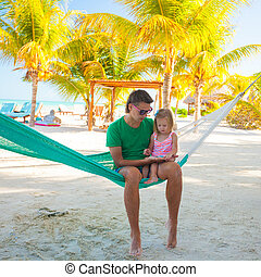 Father with little daughter on tropical vacation relaxing in hammock